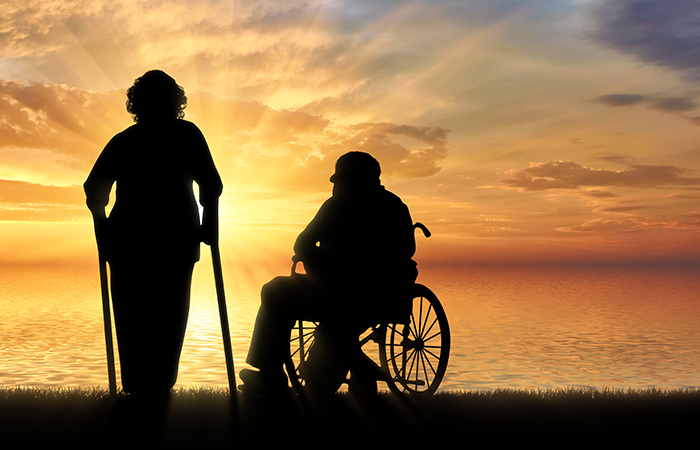 Silhouette of an old woman on crutches and elderly man in a wheelchair